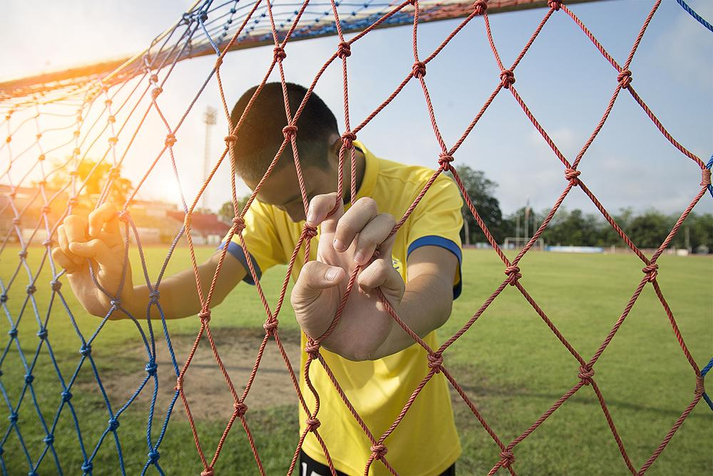 Young asian boy holding soccer goal net looking down.