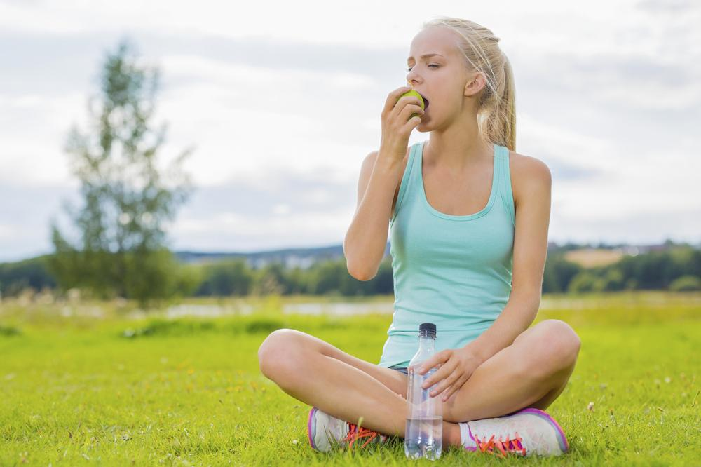 Teen girl sitting with water bottle, eating an apple.