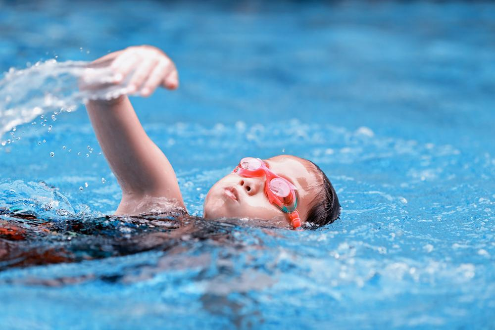 Young girl swimming with goggles on.