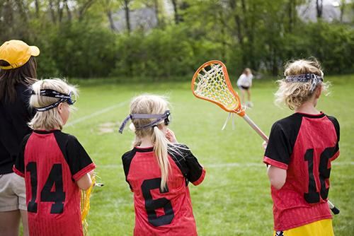 Young female lacrosse players on sideline with female coach.