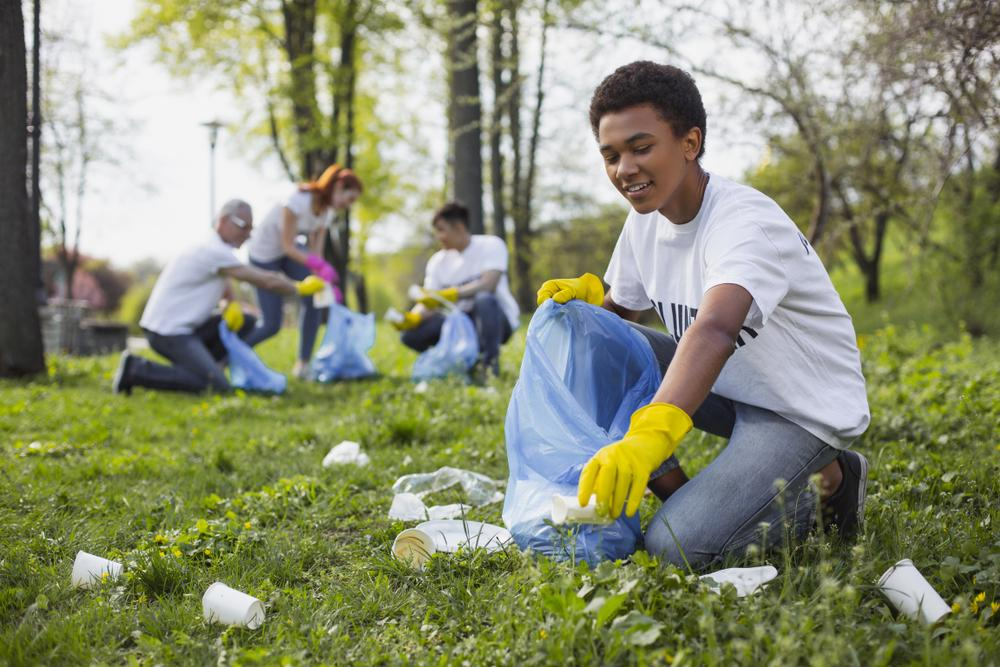 Young boy picking up trash with friends wearing gloves.