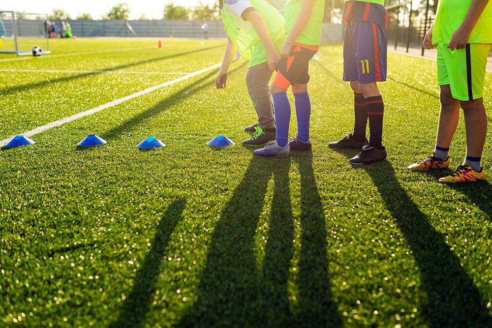 Soccer players shot from waist down about to begin training.