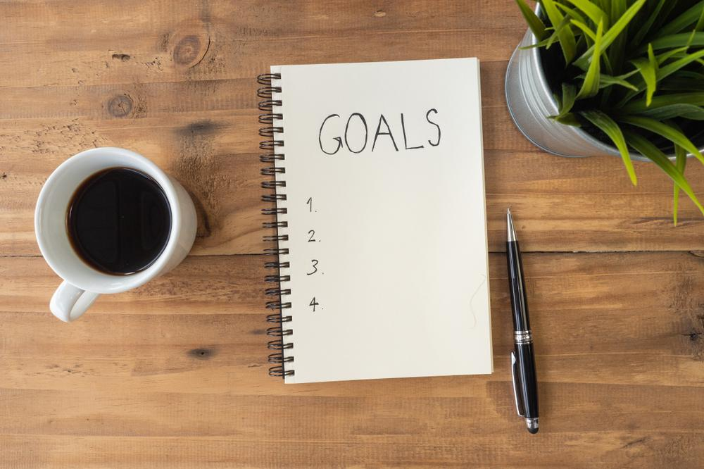 "Notebook with ""goals"" written at the top next to a pen."