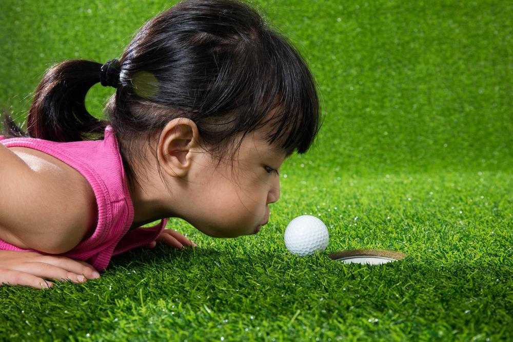 Little asian girl blowing on a golf ball to make it go in the hole.