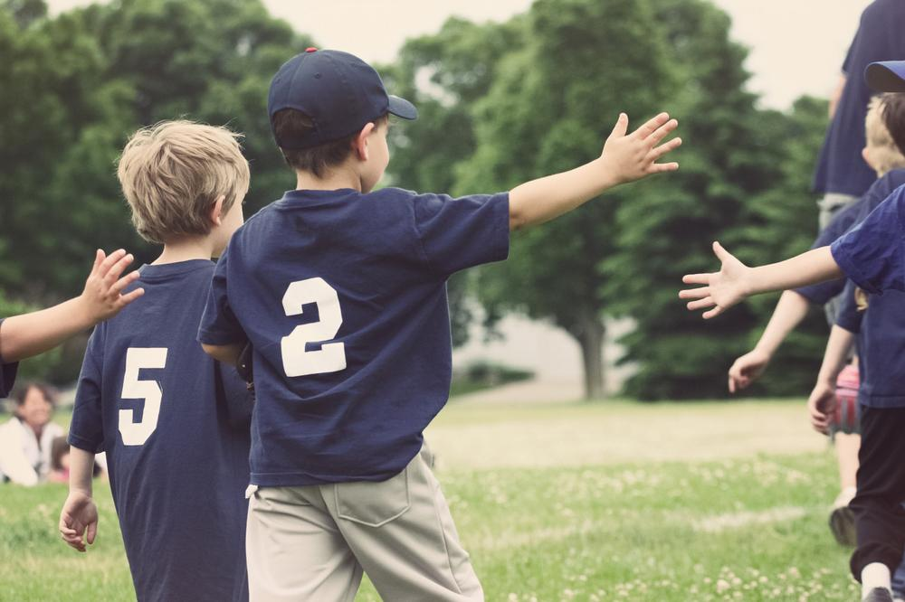 Young baseball players high fiving after game.
