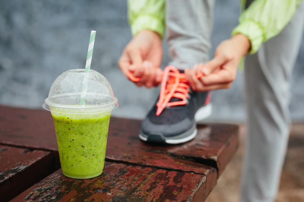 Close up of a green smoothie with someone tying a gym shoe behind it.