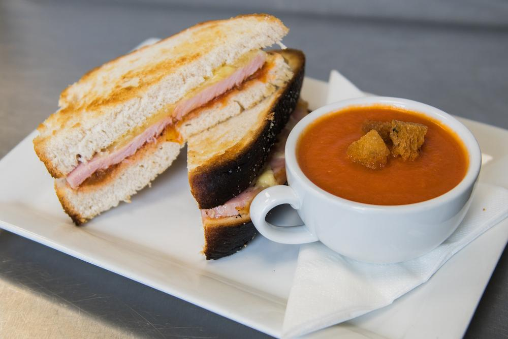 Grilled ham and cheese sandwich with a cup of tomato soup.