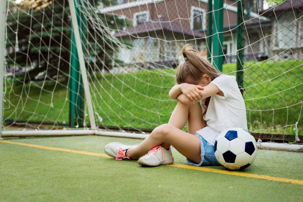 Upset young girl in front of goal next to soccer ball.
