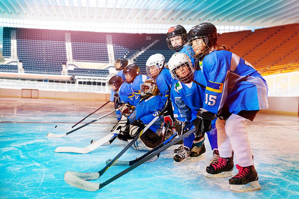 Young female hockey team together on ice.