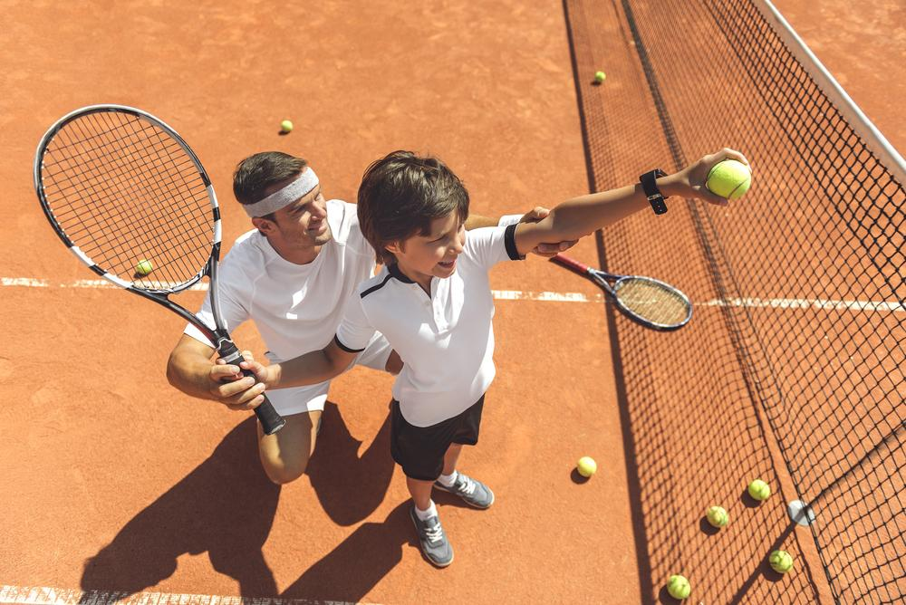 Young boy being coached on tennis.