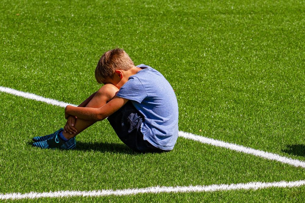 Young white boy sitting on soccer field with head on news.