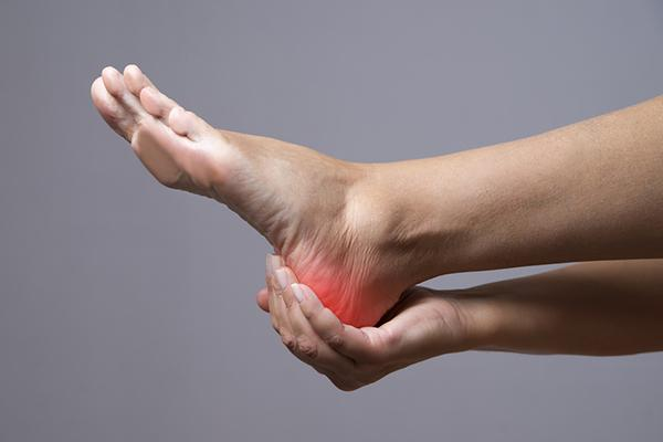 A hand holding onto a painful foot heel.