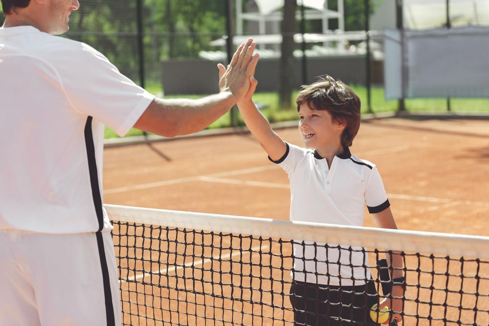 Young boy high fiving coach on tennis court.