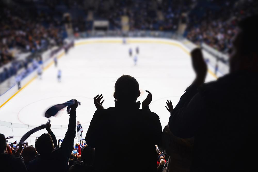 Fans shot in shadow from behind in a hockey arena.