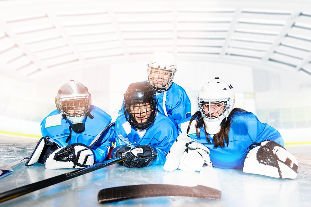 Young hockey players laying on ice together.
