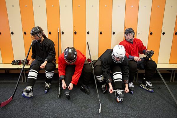 Small group of young hockey players in locker room.