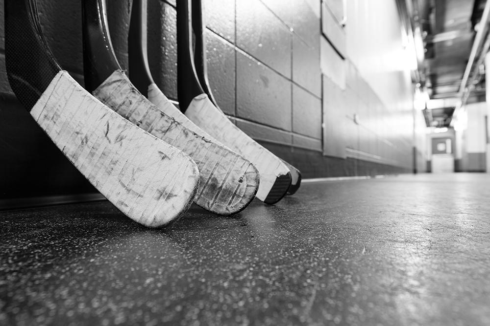 Hockey sticks lined up against a wall in a black and white image.