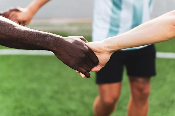 Close up of two soccer teammates holding hands.