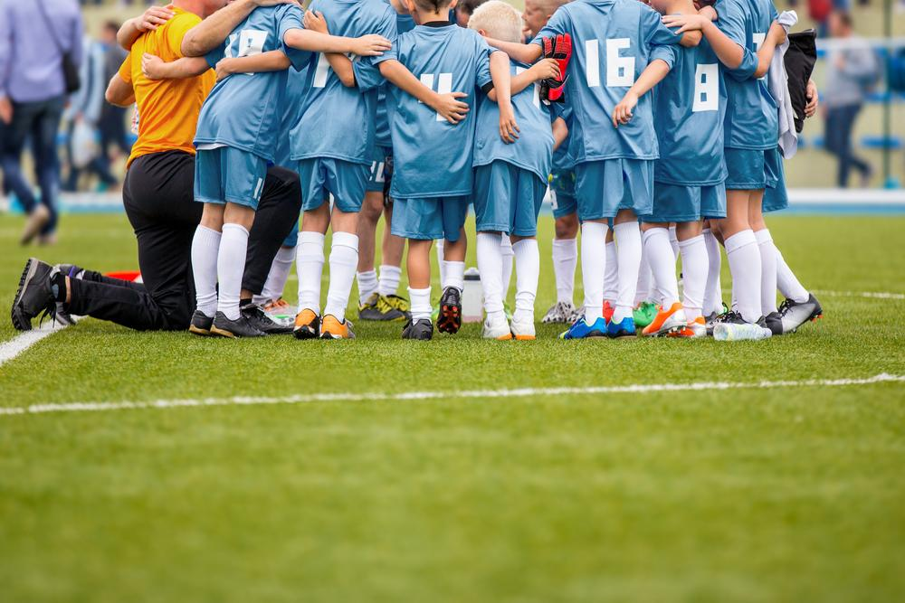 Youth soccer team in a huddle.