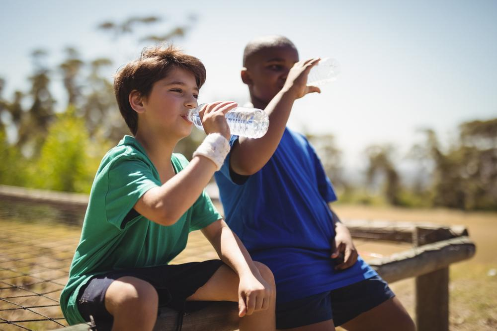 Two young boys drinking water out of water bottles on a bench outside.