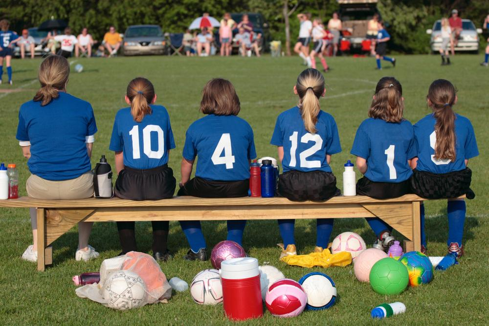Girls soccer team from behind on bench.