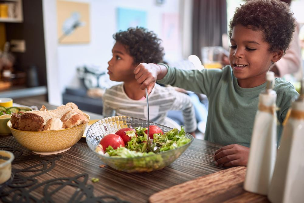 Young boys eating salad and bread at table.