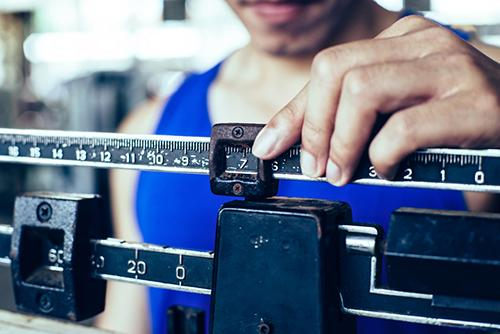 Close up of a manual body weight scale.