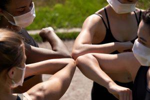 Four young diverse girls wearing face masks bumping elbows outside.