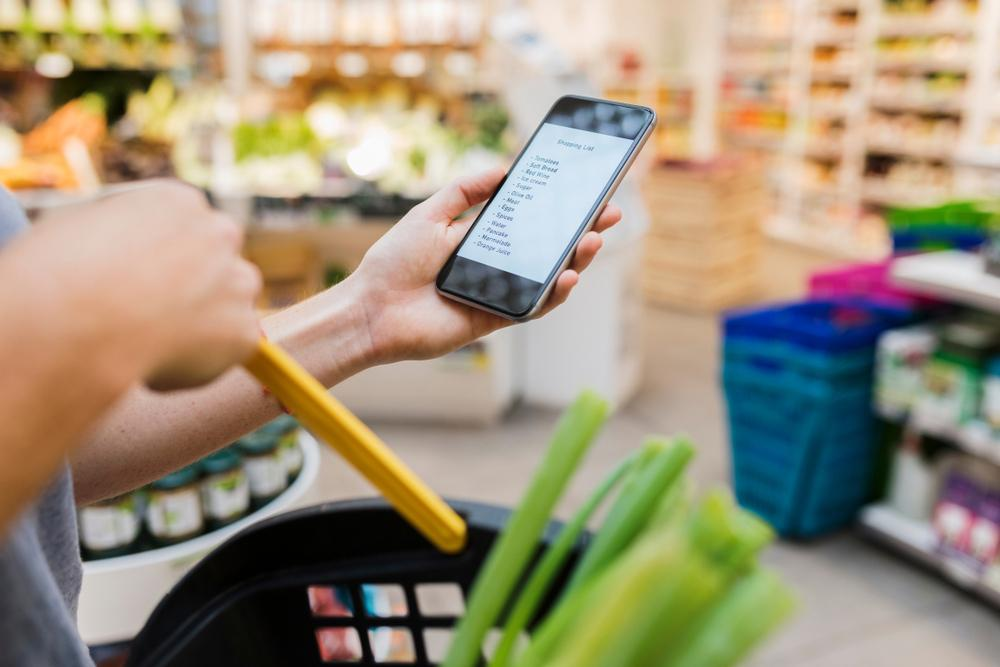 A hand holding a phone with a grocery list on it in a grocery store.