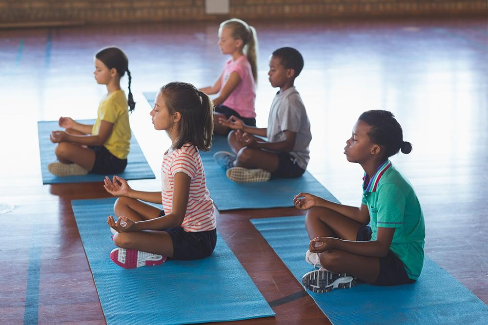 Diverse group of children sitting on yoga mats practicing meditation.
