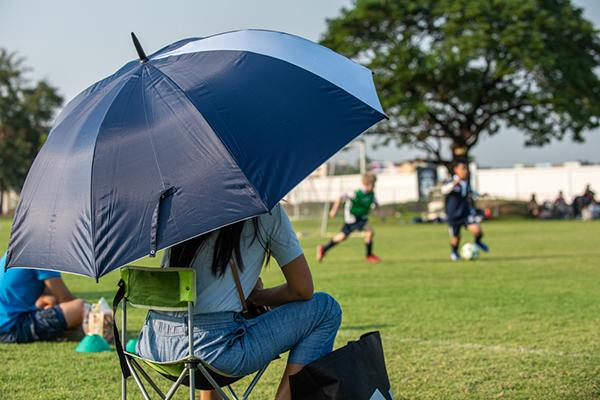 Mother sitting on sideline of outdoor soccer game.