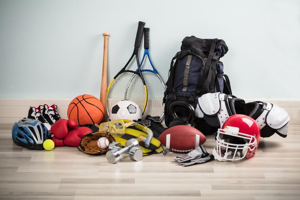 Variety of sport equipment on a floor.