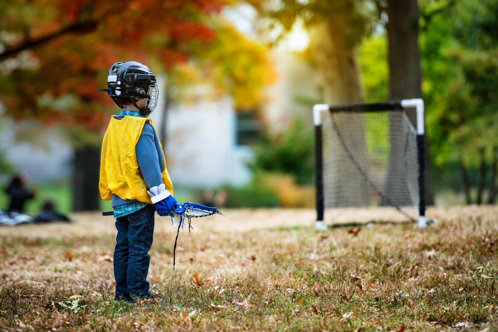 Young kid in lacrosse gear standing alone in front of a goal.