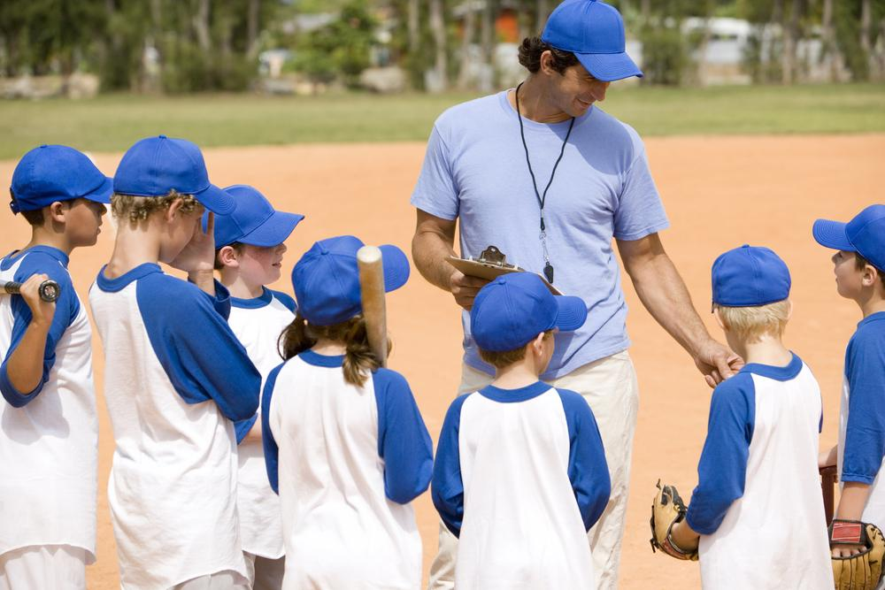 Male coach talking to young baseball team.