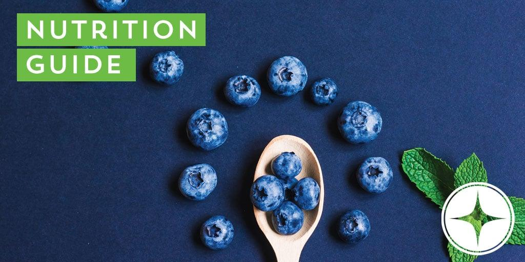 blueberries on wooden spoon on blue background