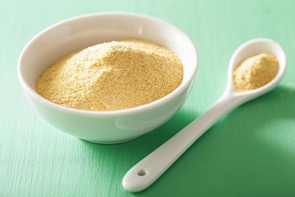Nutritional yeast in a bowl next to a spoon.
