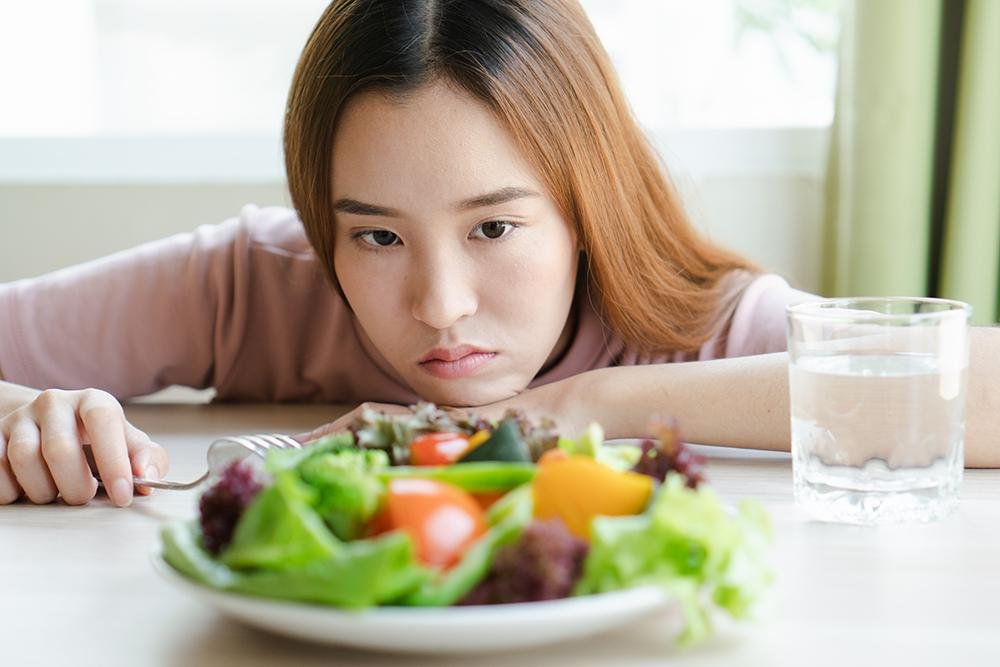 Asian female teen looking at a plate of salad.