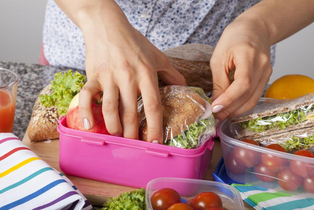 Close up of hands packing a lunch.