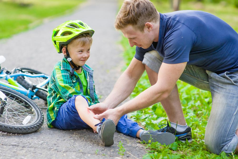 Dad helping son who hurt leg after falling off bike.