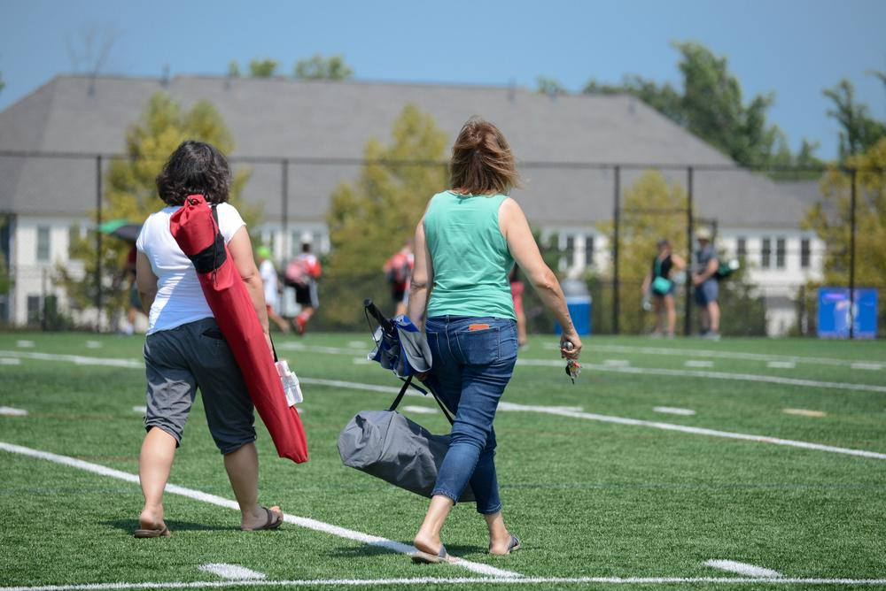 Two moms walking on a field before a youth sports game carrying chairs.