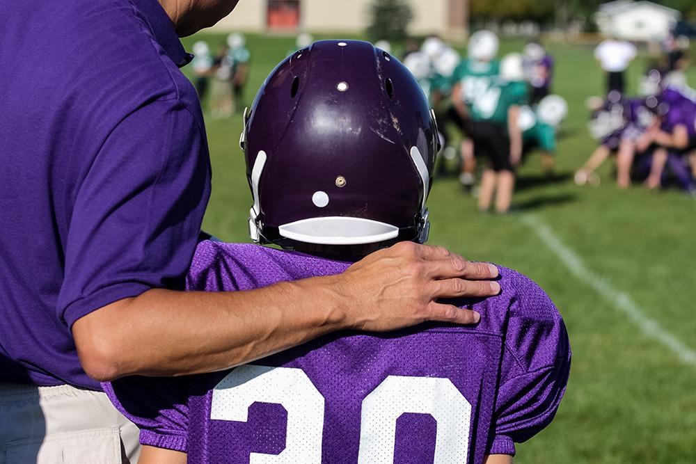 Young football player with coach by his side.