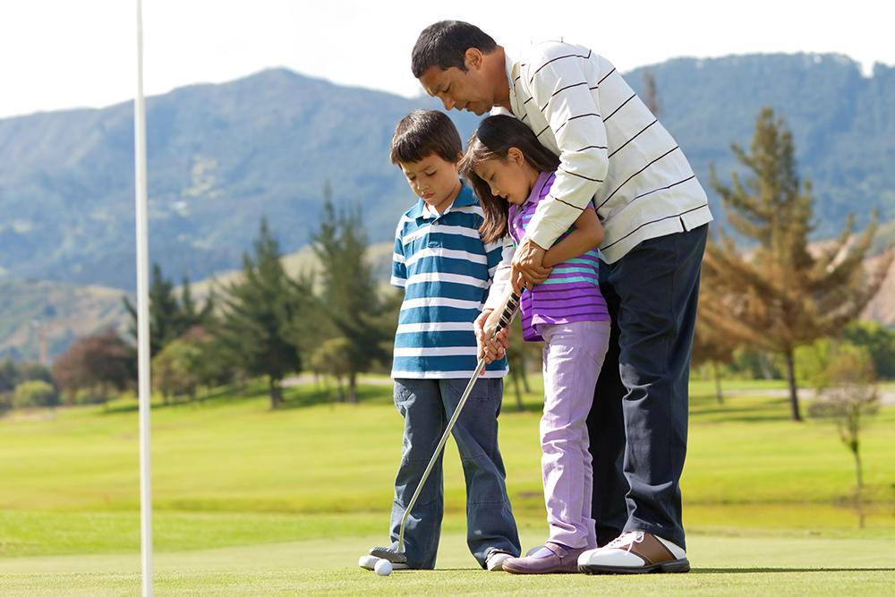 Father teaching son and daughter to golf on course.