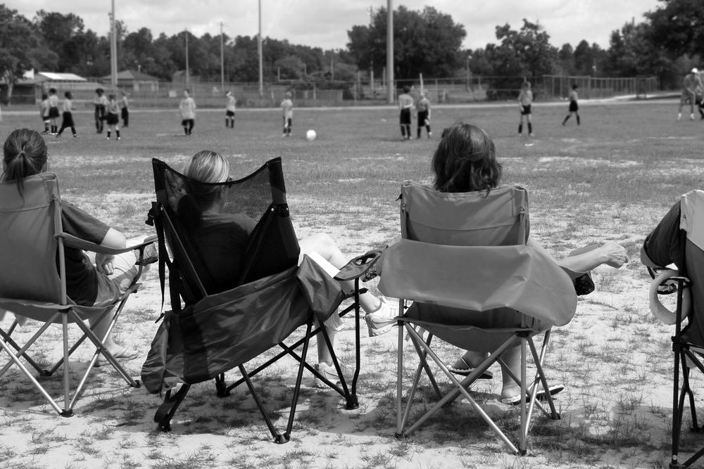 Parents sitting in chairs on sideline of child's sports game.
