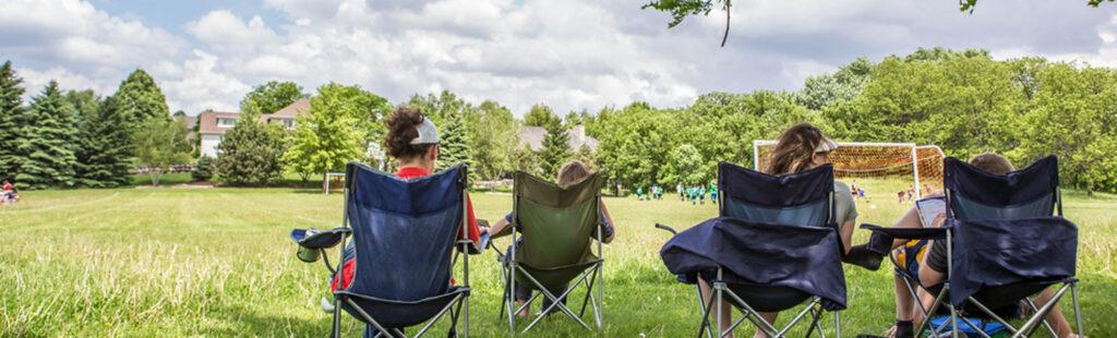 Parents sitting on sidelines of youth sports game outdoors.