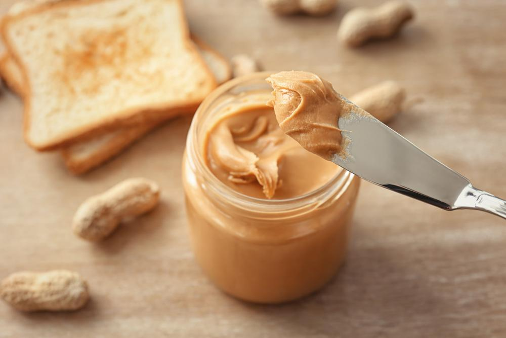 Knife taking peanut butter out of the jar.