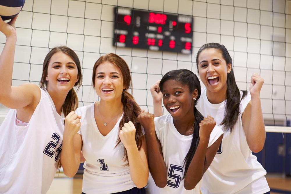 Group of diverse female teen volleyball players in front of net.