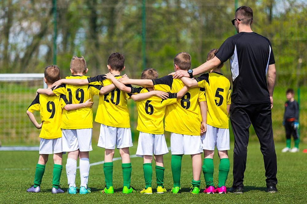 Young soccer team with arms around each other.