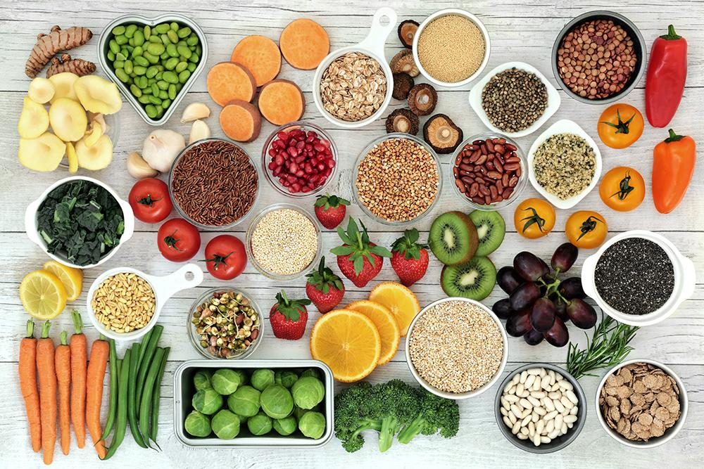 Variety of fruits, vegetables, grains, and nuts on a wood table.