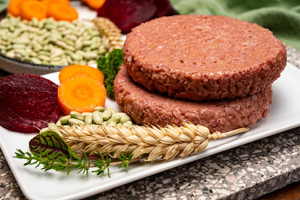 Vegan burgers next to grain and plants.