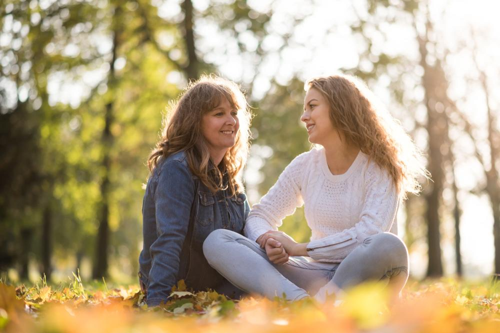 Mother sitting with teen daughter outside.